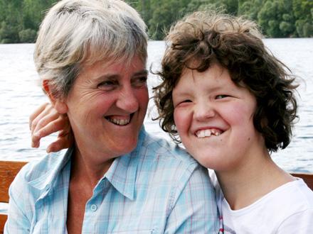 Einzelbetreuung - Begleiterin mit Kind lachend auf Bank vor See