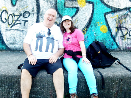 Einzelbetreuung Betreuer und Kind auf Mauer sitzend