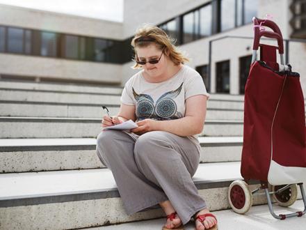 Individuelle Reisen - Frau auf Treppe schreibend