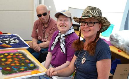 Drei Personen lächelnd vor Filzteppichen